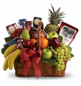 A variety of fresh fruit and gourmet foods in a beautiful gift basket
